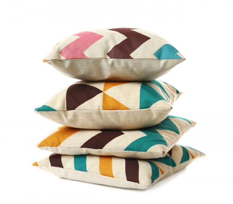 Stack of soft pillows on white background